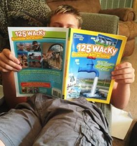 My son reading 125 Wacky Roadside Attractions, the latest Nat Geo Kids book.